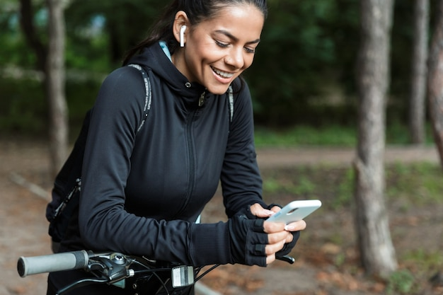 Gros Plan D'une Jeune Femme Souriante De Remise En Forme à Cheval Sur Un Vélo Dans Le Parc, écouter De La Musique Avec Des écouteurs, Tenant Un Téléphone Mobile Photo Premium