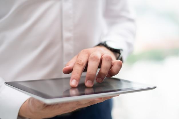Gros plan d'un jeune homme d'affaires à l'aide d'une tablette numérique Photo gratuit