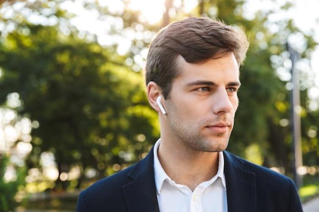 Gros Plan D'un Jeune Homme D'affaires Marchant à L'extérieur, Portant Des écouteurs Photo Premium