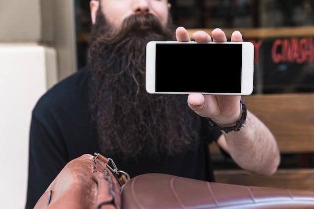 Gros plan d'un jeune homme barbu montrant l'écran du téléphone mobile Photo gratuit