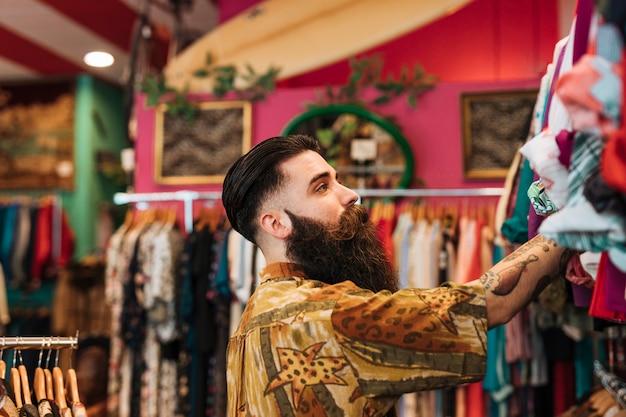 Gros Plan D'un Jeune Homme Barbu, Regardant Les Vêtements Suspendus Sur Rail Photo gratuit