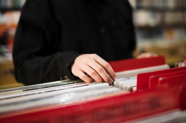 Gros plan jeune homme à la recherche de vinyles en magasin Photo gratuit