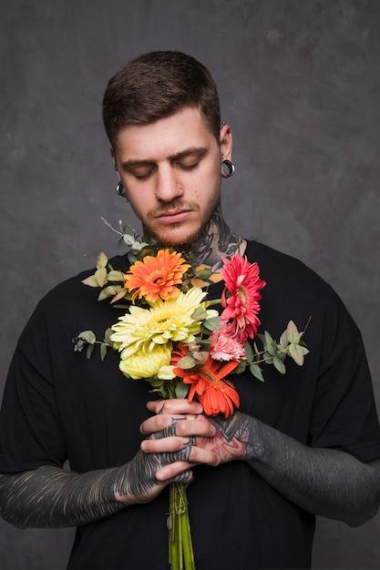 Gros plan d'un jeune homme tatoué tenant des fleurs à la main en prière Photo gratuit