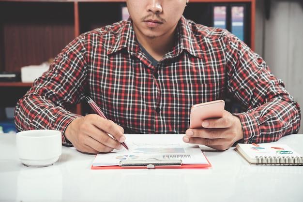 Gros plan jeune homme travaillant et smartphone et ordinateur portable Photo gratuit