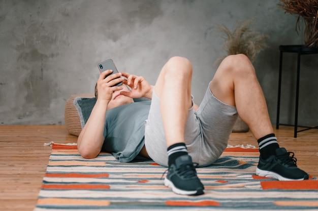 Gros Plan D'un Jeune Homme En Uniforme De Sport Repose Sur Le Sol à La Maison, Regardant Le Téléphone Sur Un Réseau Social. étudiant Flânant Et Retardant Le Travail Et Les études Photo Premium
