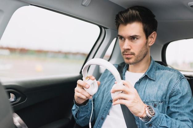 Gros plan, de, a, jeune homme, voyager, dans voiture, mettre, blanc, casque Photo gratuit