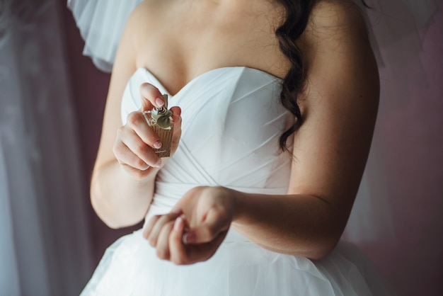 Gros plan de la jeune mariée se prépare avec des parfums à la maison le matin du jour du mariage Photo Premium