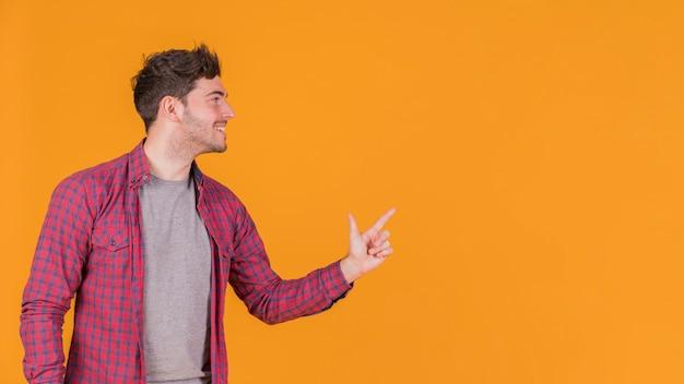 Gros plan, jeune, pointage, doigt, quelque chose, contre, orange, toile de fond Photo gratuit