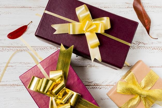 Gros plan d'un joli cadeau en boîte et feuilles sur une planche de bois peinte Photo gratuit