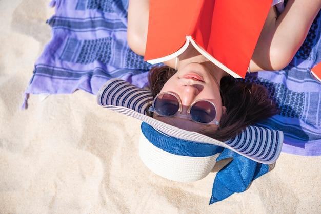 Gros plan de jolie femme couchée et lisant un livre sur la plage tropicale en période estivale. Photo Premium