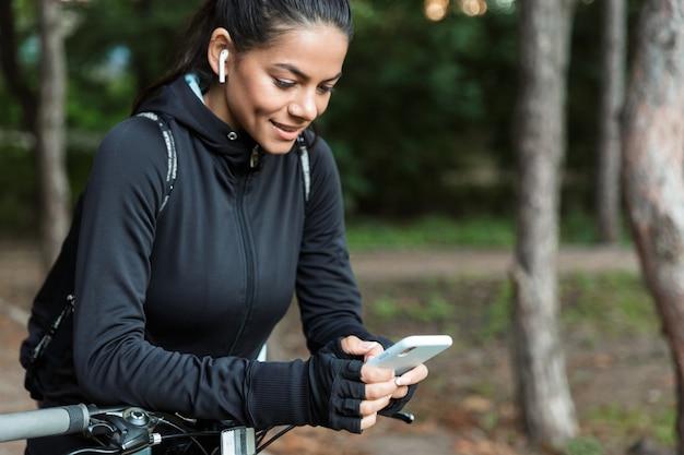Gros Plan D'une Jolie Jeune Femme De Remise En Forme à Cheval Sur Un Vélo Dans Le Parc, écouter De La Musique Avec Des écouteurs, Tenant Un Téléphone Mobile Photo Premium