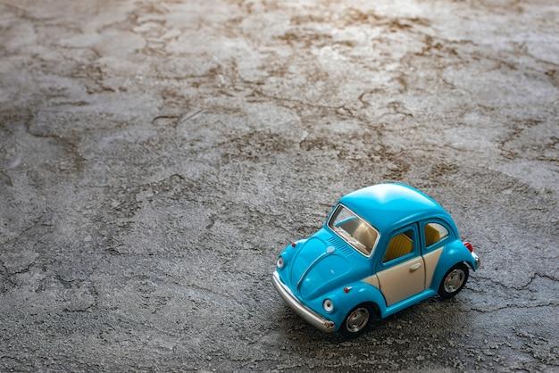 Gros plan de jouet un modèle de voiture bleue sur un fond de plâtre Photo Premium