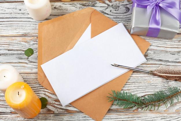 Gros plan de la lettre de noël écrit sur du papier jaune sur un fond en bois avec des décorations Photo Premium
