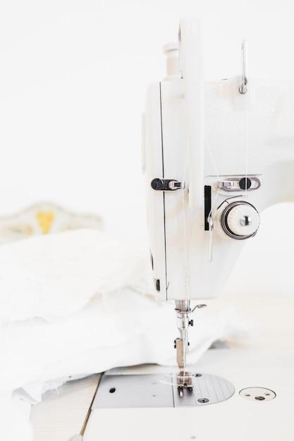 Gros plan de la machine à coudre et du tissu blanc Photo gratuit