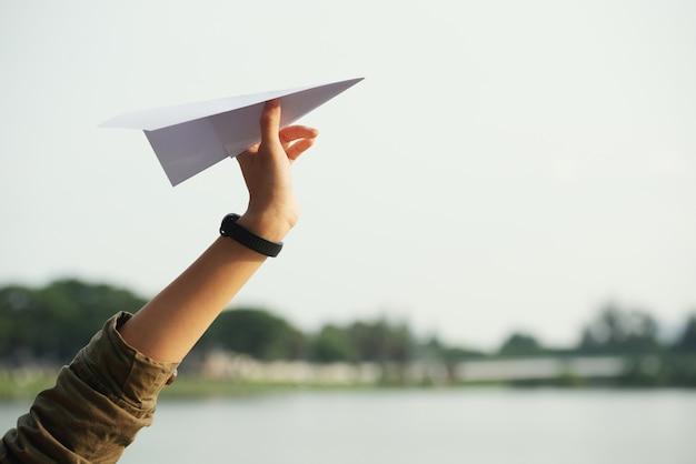 Gros plan d'une main d'adolescent jetant l'avion en papier Photo gratuit