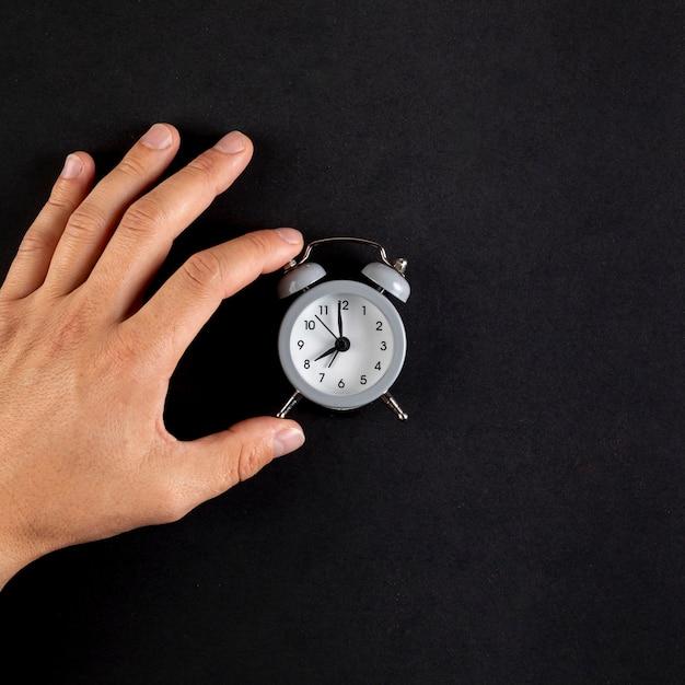Gros plan d'une main arrangeant une horloge vintage Photo gratuit