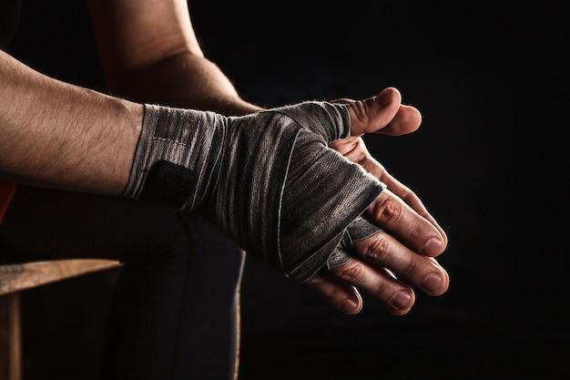 Gros Plan Main Avec Bandage De Kickboxing Formation Homme Musclé Sur Fond Noir Photo gratuit