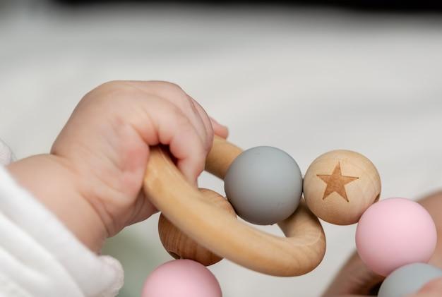 Gros plan d'une main de bébé, jouant avec un jouet en bois. Photo Premium