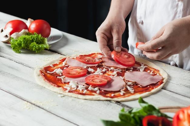 Gros Plan De La Main Du Chef Boulanger En Uniforme Blanc, Faire De La Pizza à La Cuisine Photo gratuit