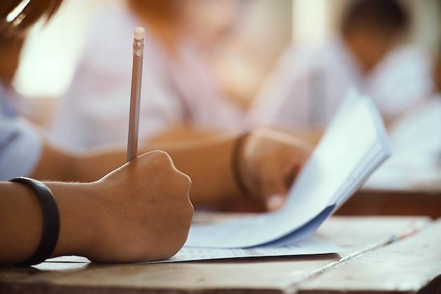 Gros plan à la main de l'étudiant tenant un crayon et prenant l'examen en salle de classe avec le stress pour le test de l'éducation. Photo Premium