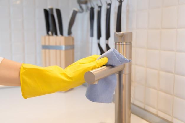 Gros plan de la main féminine dans les gants de nettoyage du robinet de cuisine Photo gratuit