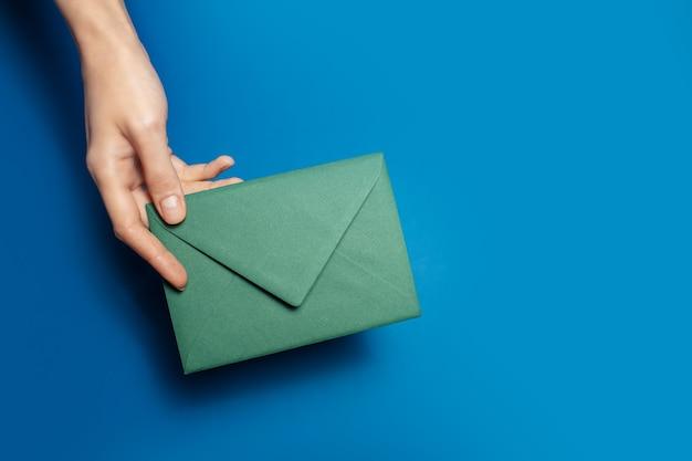 Gros plan d'une main féminine tenant une enveloppe de papier vert sur de couleur bleue. Photo Premium