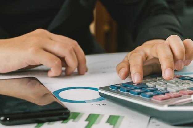 Gros plan main de femme d'affaires comptable ou banquier à l'aide de la calculatrice, calcul de la finance Photo Premium