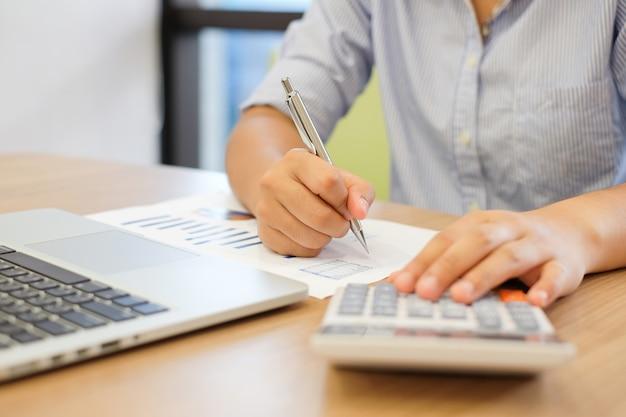 Gros plan sur la main de la femme en appuyant sur la calculatrice pour calculer l'estimation des coûts Photo Premium