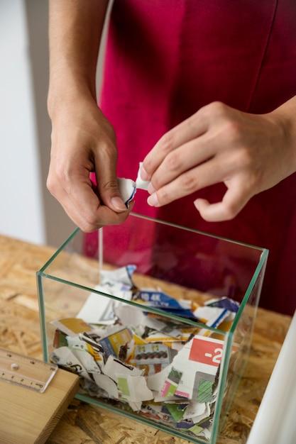 Gros plan, main, femme, déchiré, papier, verre, récipient Photo gratuit