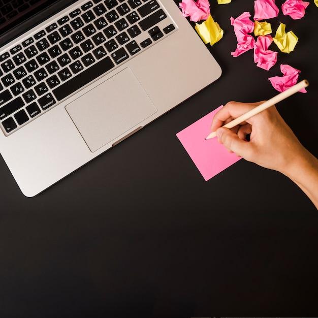 Gros plan, de, main femme, écriture, sur, note adhésive, à, ordinateur portable, et, papier froissé, sur, arrière-plan noir Photo gratuit