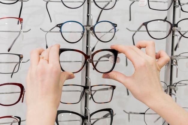 Gros plan, main femme, enlever, lunettes, affichage Photo gratuit