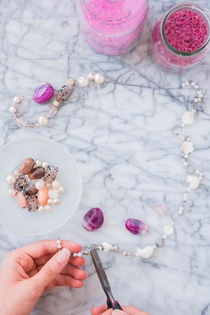 Gros plan, de, main femme, fabrication, bijoux, perles, pince, sur, marbre, fond texturé Photo gratuit