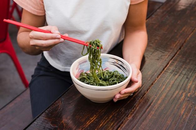 Gros plan, main femme, manger, algue verte, à, baguettes rouges Photo gratuit