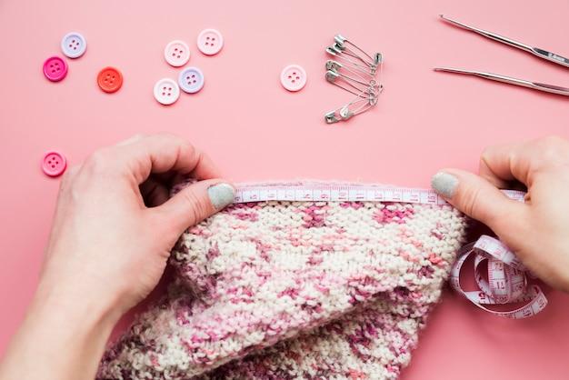 Gros plan de la main de femme mesurant le tricot avec des boutons; épingles de sûreté et aiguille au crochet Photo gratuit