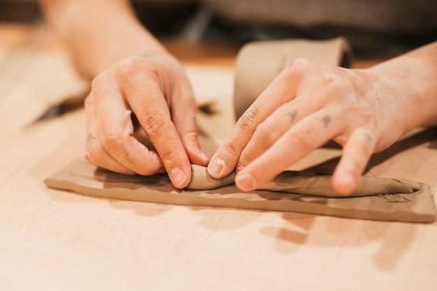Gros plan, main femme, mouler, argile, sur, table bois Photo gratuit