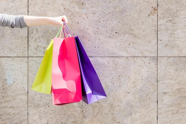 Gros plan d'une main de femme avec des sacs colorés devant le mur Photo gratuit