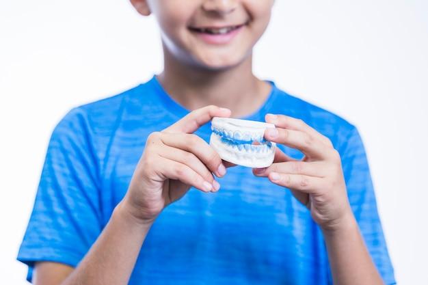 Gros plan, de, main garçon, tenue, dents, plâtre, moule Photo gratuit