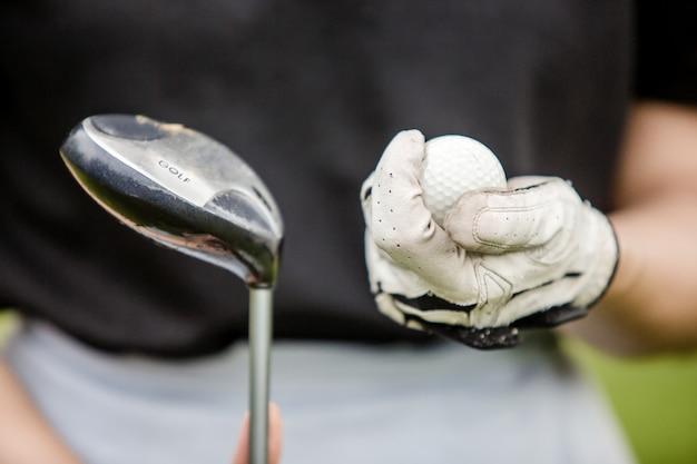 Gros plan de la main d'une golfeuse tenant une balle de golf et une tête de club Photo Premium