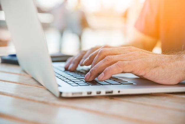 Gros plan main homme dactylographie ordinateur portable sur les