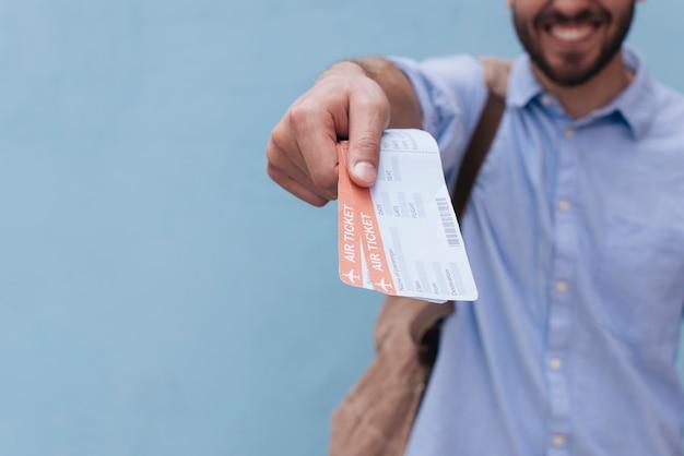Gros plan de la main de l'homme montrant le billet d'avion sur fond bleu Photo gratuit