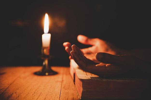 Gros plan, la main de l'homme prie dans l'église avec une bougie allumée Photo gratuit