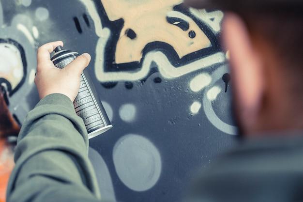 Gros plan, de, a, main homme, pulvérisation, peinture, sur, graffiti, mur Photo gratuit