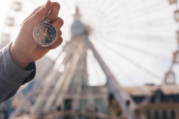 Gros plan, de, main humain, tenue, navigation, compas, sur, défocaliser, fond, de, grande roue Photo gratuit