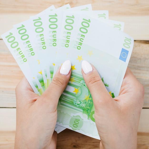 Gros plan, de, main humaine, tenue, cent, euro, billets banque, sur, table bois Photo gratuit