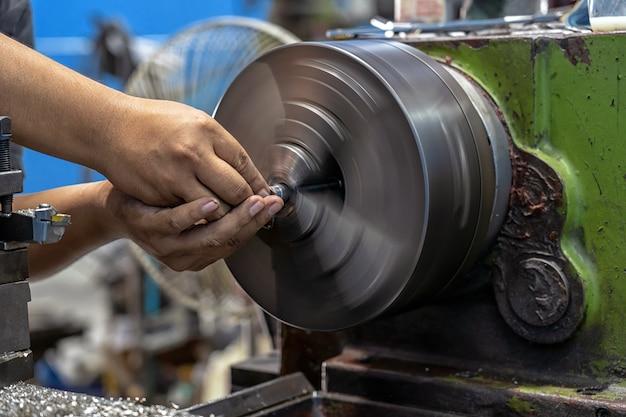 Gros plan d'une main de machiniste travaillant avec des tours à une machine Photo Premium