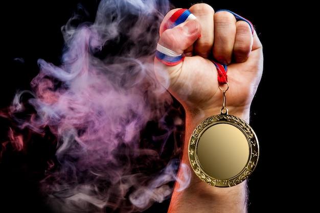 Gros plan d'une main masculine forte tenant une médaille d'or pour un exploit sportif Photo Premium