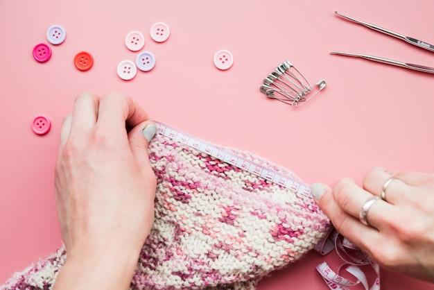 Gros plan d'une main mesurant le tricot avec du ruban adhésif sur fond rose Photo gratuit