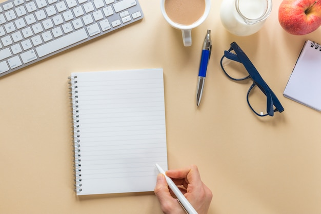 Gros plan, main, personne, écriture, spirale, bloc-notes, stylo, beige, bureau, bureau Photo gratuit