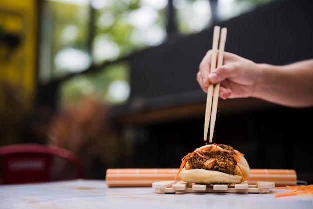 Gros plan, main, personne, manger, gua bao, baguettes, sur, plateau bois Photo gratuit