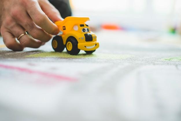 Gros plan de la main avec une petite voiture jaune Photo gratuit